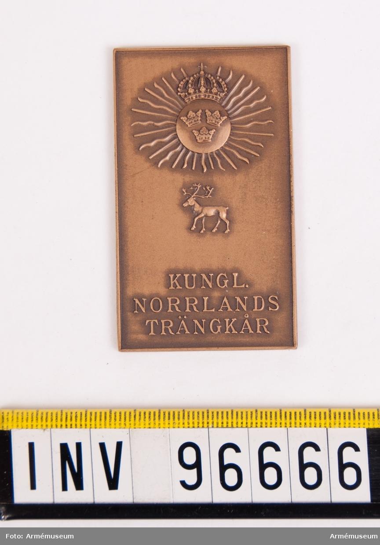 Plakett i brons för Norrlands trängkår. Stans nr 19922, härdad 1948-08-14. Plakett, 37x63 mm, åtsida m. kårens vapen, 3-kronor på rund sköld, krönt av kunglig krona, jämte strålar samt därunder ren, nedtill inskription KUNGL. NORRLANDS TRÄNKÅR, plaketten omgiven av upphöjd kant.