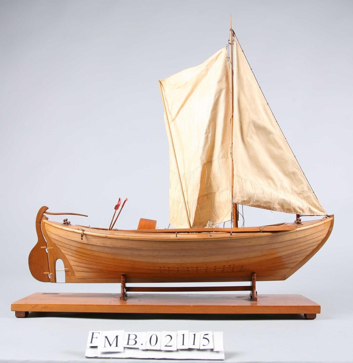 Modellbåt med mast og to seil. Den har 3 årer, 2 bøyer, et garn og en dregg.