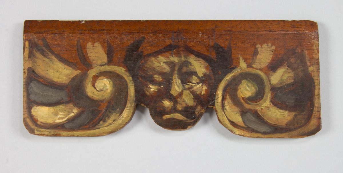 Schaslong av trä med 6 skulpterade framben och två skulpterade bakben. Mellan varje ben skulpterad framslå med växtmotiv respektive maskaron. Tassfötter. Tvärslå mellan fram- och bakben. Hel rygg och ett sidostycke med pilastrar. Fast hög resårbotten klädd med röd och vitrandigt bolstervar. Rygg- och sidostycken klädda med fastspikat blått bomullstyg och tunn stoppning. Svartmålad samt viss guldfärgad dekor. Schäslongen sammansatt av äldre möbeldelar, troligen tre stolar, insatta i senare tillverkad stomme.