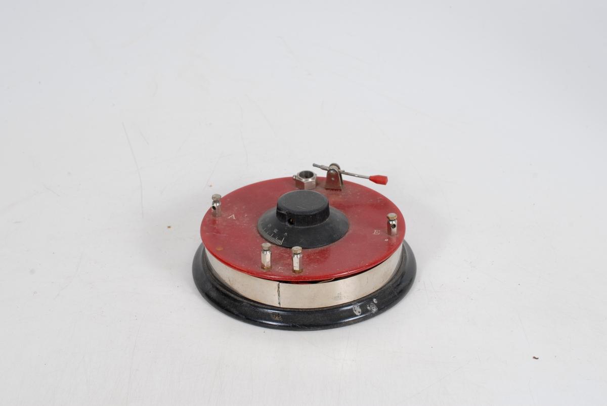 """Form: Sirkulært med treplate i bunnen           *23 Forniklet metall. Rødt """"plastlokk"""". I sentrum av lokket er det bølgevender i sort """"plast"""" m/skala. Ved kanten er det to skrufester for strøm - merket A og E. To skruer til feste for høreapparat merket T. Likeså er det feste til krystallen, og en hendel til å slutte kretsen mellom krystall og strøm."""