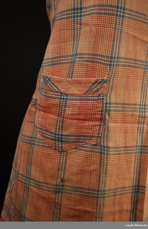 Forkleet har en liten lomme på venstre side. Forkleet er hjemmesydd, og er slitt.