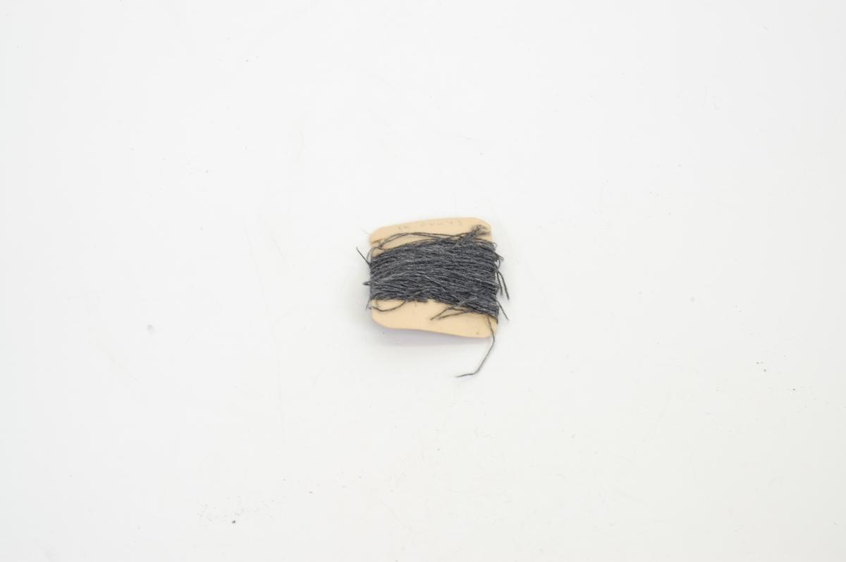 Form: avlang papplate med avrunda hjørner, garn surra rundt