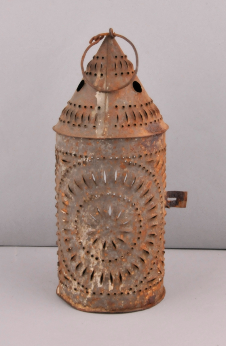 Sylinderforma nederst, rombe øvst. Gjennomhola mønster. Dør i sida med rektangulær opning midt i.  Inni ein lyshaldar.  Berehank i form av ein ring i toppen.