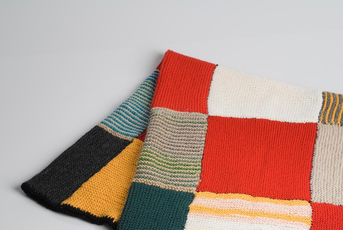 Ullteppe sydd sammen av strikkede firkanter i røde, hvite og grå farger