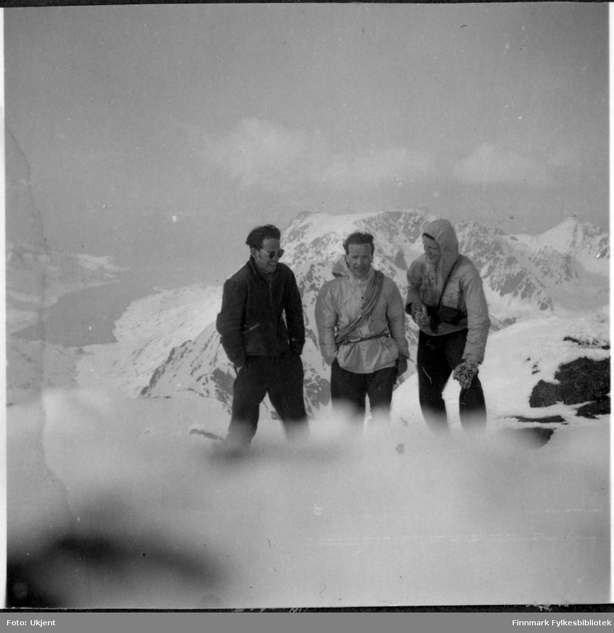 På tur til Øksfjordjøkelen i Nuvsvåg. Fra venstre Gunnar Ørstadvik, Adolf Blone og Reidar Martinsen. De tre mennene har på seg vinterklær, jakker og bukser. Gunnar helt til venstre har på seg solbriller og man kan se at Reidar helt til høyre har på seg votter. Bak mennene kan man se fjell og vann. Det er mye sne på bakken.