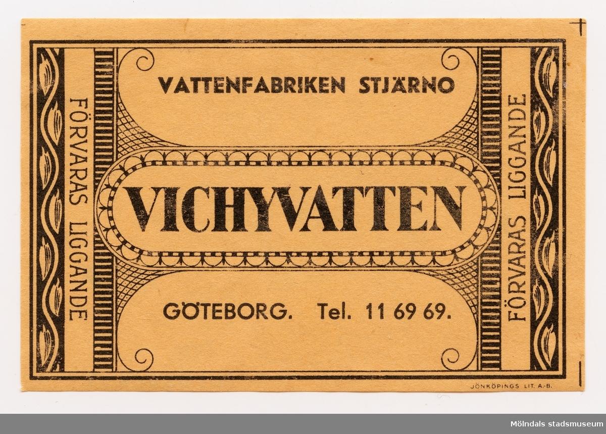 """Etikett med texten Vichyvatten Vattenfabriken Stjärno  Göteborg Tel. 11 69 69.  På kortsidorna står även texten """"Förvaras liggande"""".  Längst ner på etiketten i liten stil:Jönköpings Lit. A-B  Ingår i samling av 14 etiketter från Vattenfabriken Stjärno."""