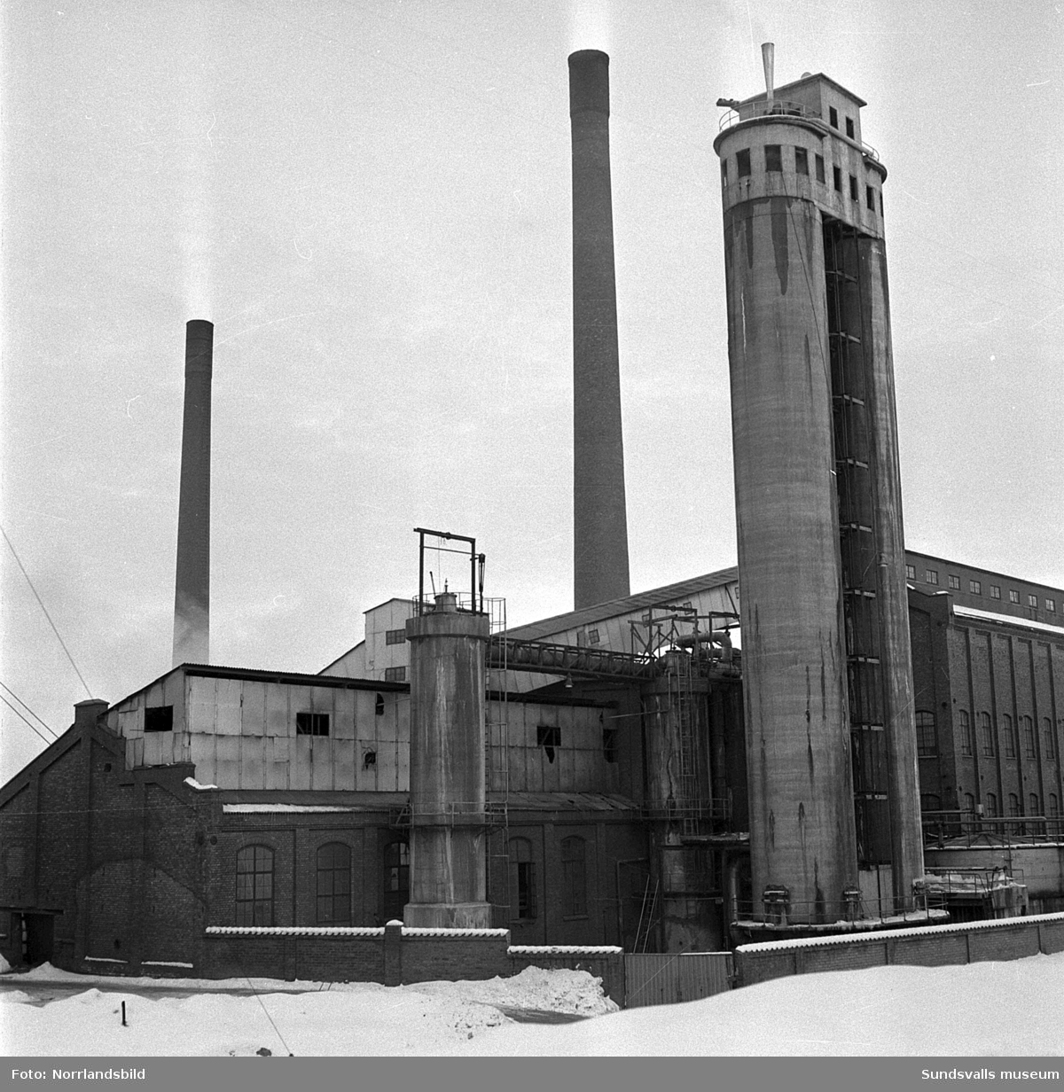 Bilder till ett nyhetsreportage om  när 24-årige Kjell Björk, som var reparatör vid Skönsmons mekaniska verkstad, av misstag blev instängd i en 68 meter hög skorsten vid Svartviksfabriken. Björk hade jobbat med att sätta in en ny ventil i rökgången till en av pannorna och blev sedan fast i skorstenen i 15 timmar. Som tur var uppfattade två fabriksarbetare på morgonen, strax innan pannan skulle köras igång igen,  hans desperata bultningar på den stängda luckan och han kunde räddas från en säker död. På första bilden är det Tore Kvistberg som demonstrerar hur det såg ut då Björk kröp ur sitt sotiga fängelse. Utanför luckan sittande på huk är Verner Mattsson och Elmer Landell, vilka var de två som räddade Björk. Enligt artikeln hade Kjell Björk fått tillbringa två timmar i badkaret för att tvätta bort allt sot.