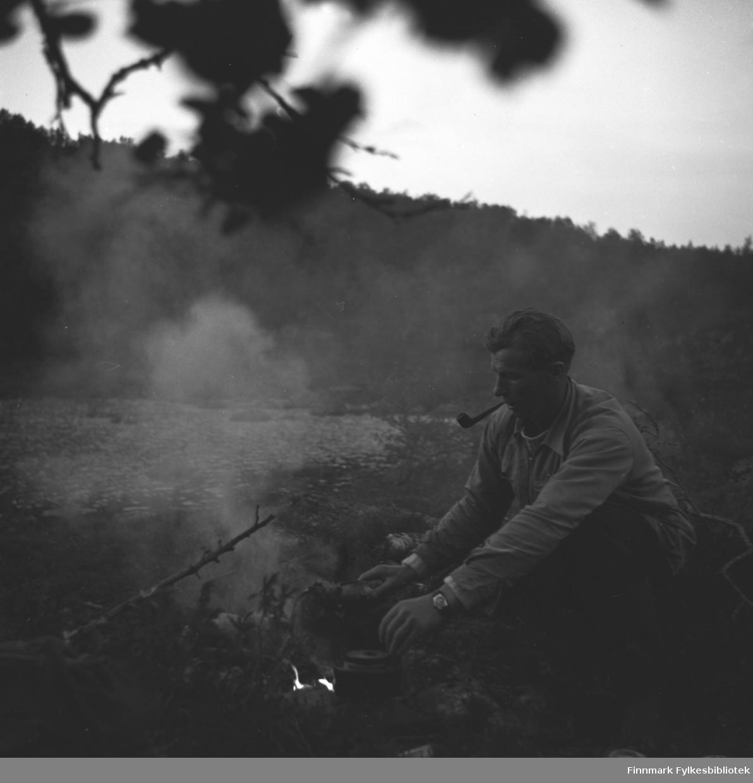 Eino Drannem sitter ved et leirbål og koker kaffe mens han røyker pipe.