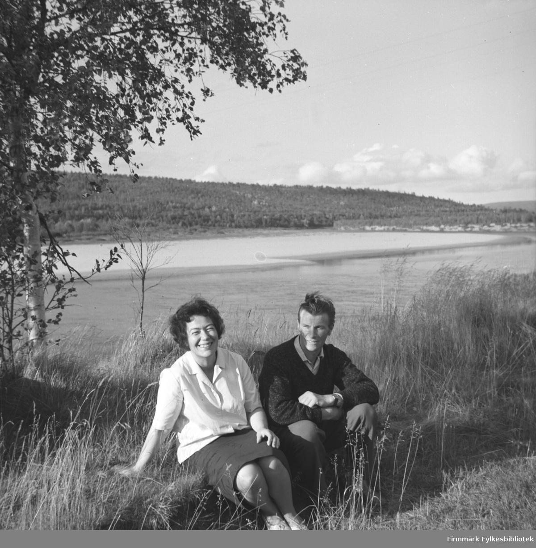 Jenny og Eino Drannem sitter ved bredden av Neidenelva.