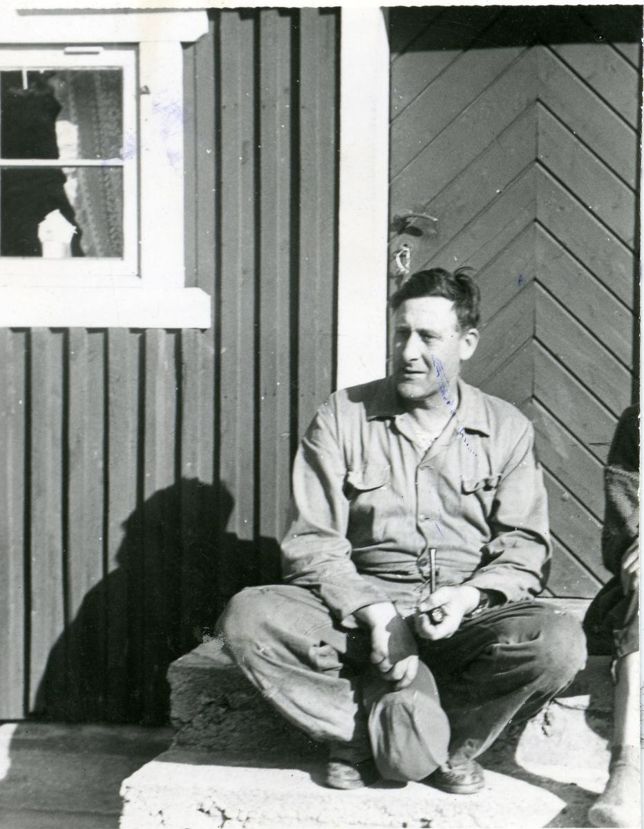 Portrett av Gudbrand Ildjarnstad sittende på trappen på hytta si i Vassfaret.