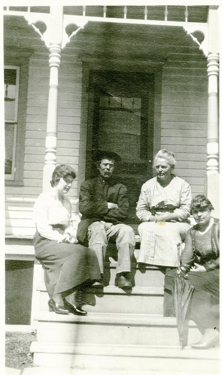3 kvinner og en mann sittende i ei trapp. Bildet er tatt i Amerika. Fra venstre:Gurine og Per (Peder) Islandsmoen, Mable og Sara.