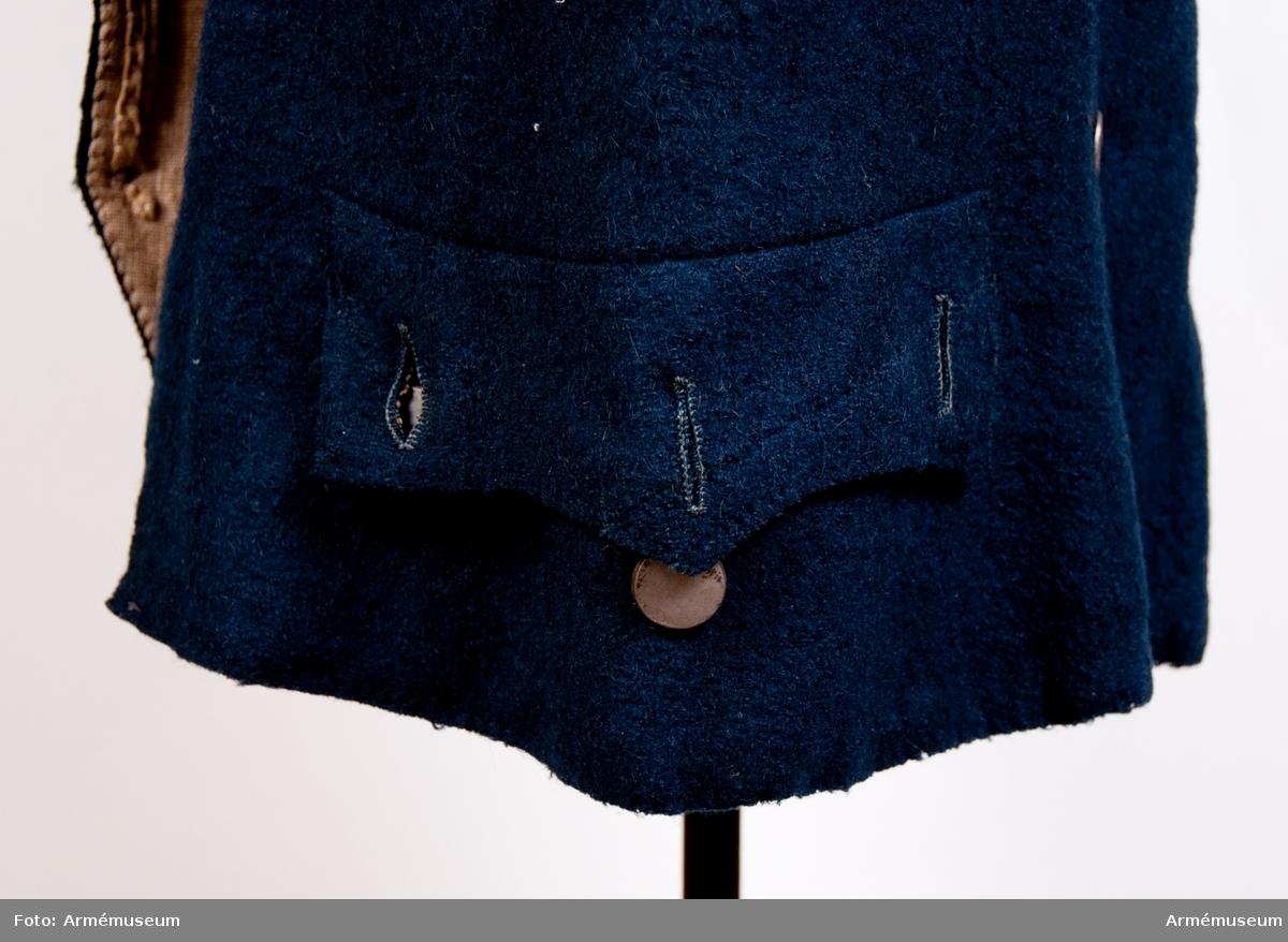 Grupp C I. Av blått kläde. På överdelen är den tvåradig med åtta knappar i varja rad och under midjan sitter två knappar i en rad. Knapparna är fastsydda vid rockens på ett speciellt sätt: genom knappöglorna går ett band,som är fastsytt vid jackan  och på vars baksida vid midjan finns två knappar. Foder av grov lärft. På framsidan sitter två fickor med treuddigt lock med knappar. Fickorna är 210 mm breda. Knapparna är av vit metall, d: 15 mm. Kragen är upprättstående, 15 mm cm hög av samma blå kläde. Ärmuppslagen har sprund och en knapp på varje.
