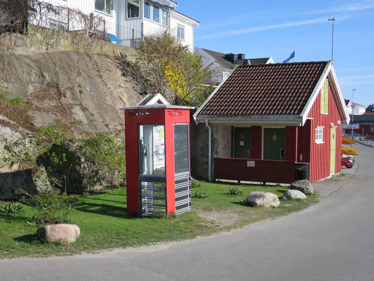 Telefonkiosken står på Drøbak båthavn, og er en av de 100 vernede telefonkiosker i Norge. De røde telefonkioskene ble laget av hovedverkstedet til Telenor (Telegrafverket, Televerket). Målene er så å si uforandret.  Vi har dessverre ikke hatt kapasitet til å gjøre grundige mål av hver enkelt kiosk som er vernet.  Blant annet er vekten og høyden på døra endret fra tegningene til hovedverkstedet fra 1933. Målene fra 1933 var: Høyde 2500 mm + sokkel på ca 70 mm Grunnflate 1000x1000 mm. Vekt 850 kg. Mange av oss har minner knyttet til den lille røde bygningen. Historien om telefonkiosken er på mange måter historien om oss.  Derfor ble 100 av de røde telefonkioskene rundt om i landet vernet i 1997. Dette er en av dem.
