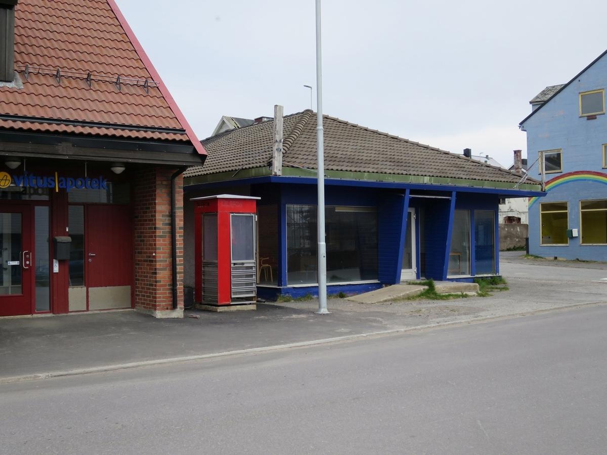 Denne telefonkiosken står i Strandgaten 28 i Vardø, og er en av de 100 vernede telefonkioskene i Norge. De røde telefonkioskene ble laget av hovedverkstedet til Telenor (Telegrafverket, Televerket). Målene er så å si uforandret.  Vi har dessverre ikke hatt kapasitet til å gjøre grundige mål av hver enkelt kiosk som er vernet.  Blant annet er vekten og høyden på døra endret fra tegningene til hovedverkstedet fra 1933. Målene fra 1933 var: Høyde 2500 mm + sokkel på ca 70 mm Grunnflate 1000x1000 mm. Vekt 850 kg. Mange av oss har minner knyttet til den lille røde bygningen. Historien om telefonkiosken er på mange måter historien om oss.  Derfor ble 100 av de røde telefonkioskene rundt om i landet vernet i 1997. Dette er en av dem.
