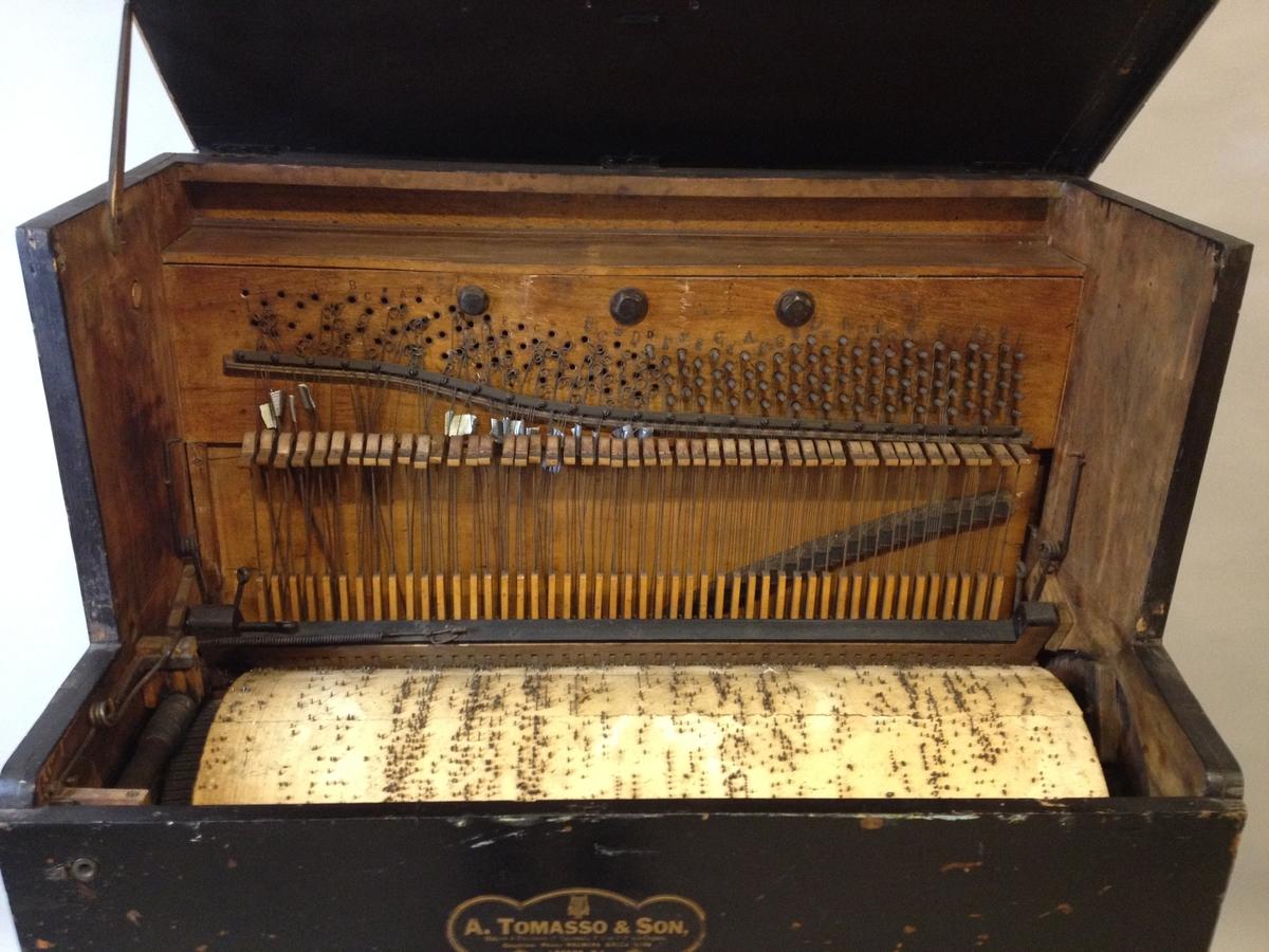 """Omfang: Mekanisk piano med papirbeklett stiftvals og med hammermekanikk. 48 hammere som slår på opprettstående strenger.  Kasse: i tre. svartmalt. håndtak av messing på hver side.   Klangbunn av nåletre(?) årringer vertikalt mot strenger. Stol med backpinning, delt i bass v . """"B""""/""""c"""". Metallplate for anhangslist.   To-korig 9 toner i bass, for øvrig 3 strenger / tone. Trykte tonenavn: """"D"""", """"E"""", 4 umerkte, [sanns F?, F#?, G?, A?, ] """"B"""", """"C"""", """"#"""".   deretter """"C, - , -, E. F. #, C, ..se skjema  Enkel mekanik, ryttere skyves sideveis (fjærbelastet) ved skifte av melodi.filtklette hammere.   Ingen synlig demping.  Mekanikkdel Sylinder med stift av jern. 838 bred x ca 32 cm i diameter (estimert). Spårbredde ca 17,5 mm 10  melodier som skiftes ved å vri på en spak t.v. på siden, merket 1-9, samt 0. stiftvals merket i bassen med linjer utmed bevegelseretningen 2-3 / tone for de føste ca 8 tonene. Notert sifrer (takter?) utmed linjene, samt markert """"Tune"""" på to steder, sekundært(?)"""