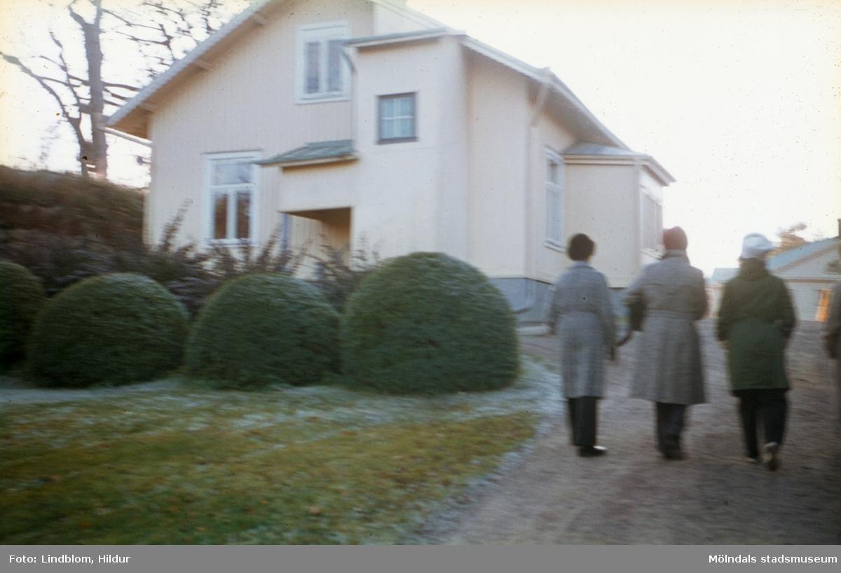 Tre kvinnor promenerar förbi vaktmästarbostaden, tidigare trädgårdsmästarbostaden, tillhörande Gunnebo slott. Mölndal, 1960-1970-tal. Fotografens far arbetade här. Till höger skymtas även del av slottets östra fasad.  För mer information om bilden se under tilläggsinformation.