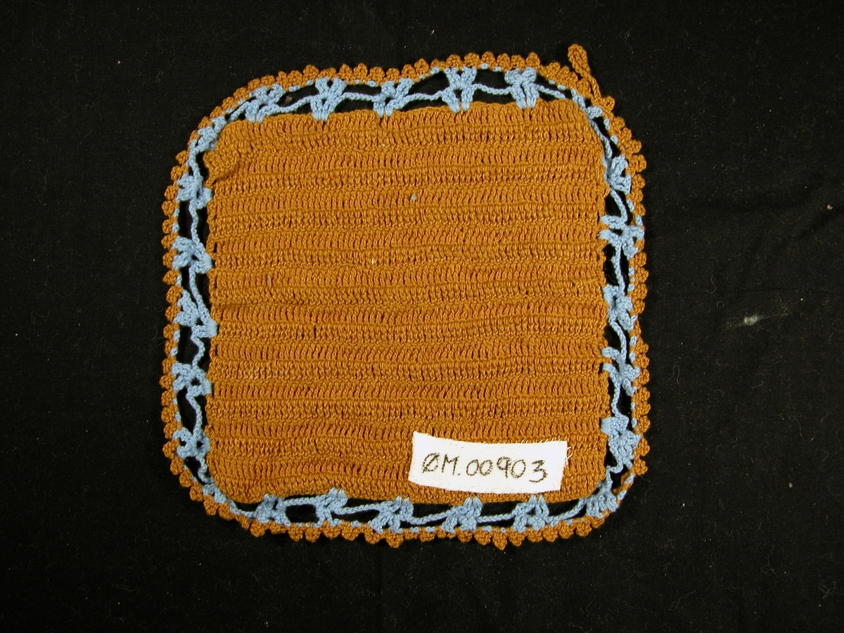 To lag: Mønsterlag: to sirklar i brun. Fire 3-bladsmotiv i blå. Rutemønster i brun, blå kant, brun kant ytst med hempe i. Bakgrunnen er brun.
