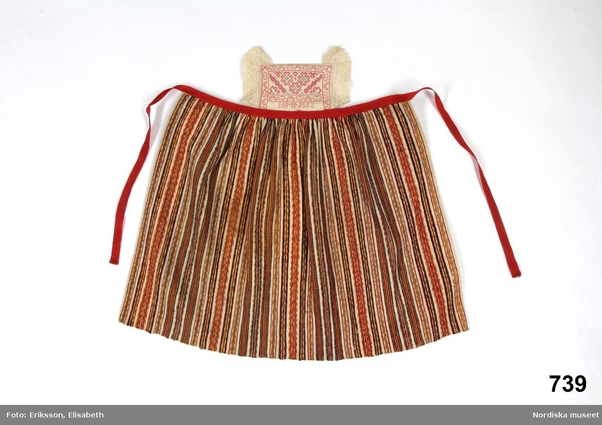 Förkläde till barnkolt för pojke.  Midjeförkläde av halvylle  på vit linvarp, livlig randning i  många färger  rött, gult, grönt, blått mm av ullgarn och bomullsgarn i blandning, rynkat i midjan mot ett  rött ylletrikåband som knyts i ryggen.  Fastsydd bröstlapp av vit bomullslärft, dubbelt tyg med heltäckande broderi i  utdragssöm s.k. stopphålssöm i rosa, ljusblått och vitt bomullsgarn inom en bård  i korssöm i rosa, märkt MNS 1852, bröstlappen kantad på sidorna med 3,5 cm bred maskingjord spets.  Handsydda fållar på sidorna i nederkant stadkant. Hör till blå kolt inv.nr  /Berit Eldvik 2013-02-19