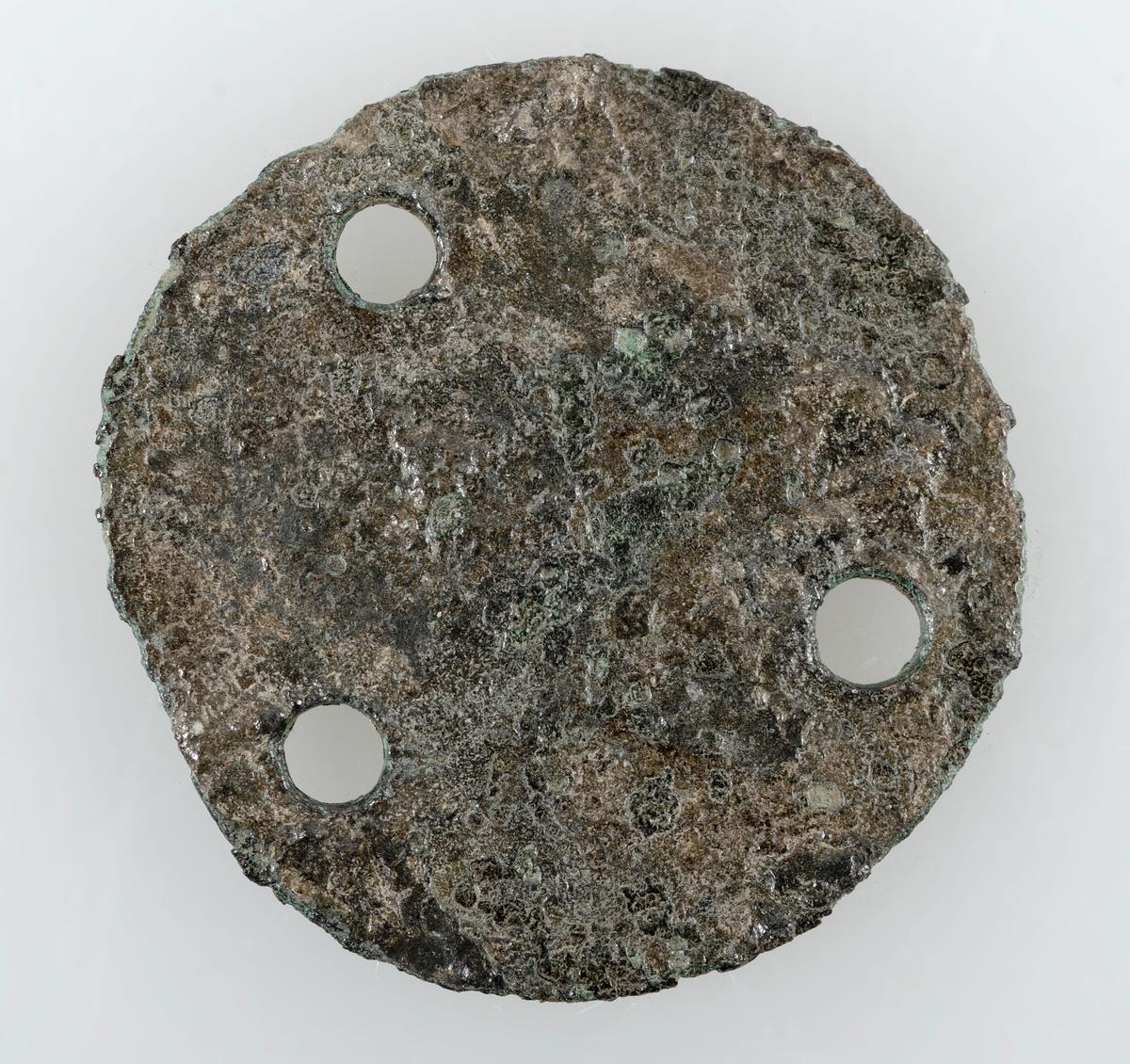 Runt myntliknande föremål av silver. Ej mynt. Med 3 hål. Möjligen en räknepenning.