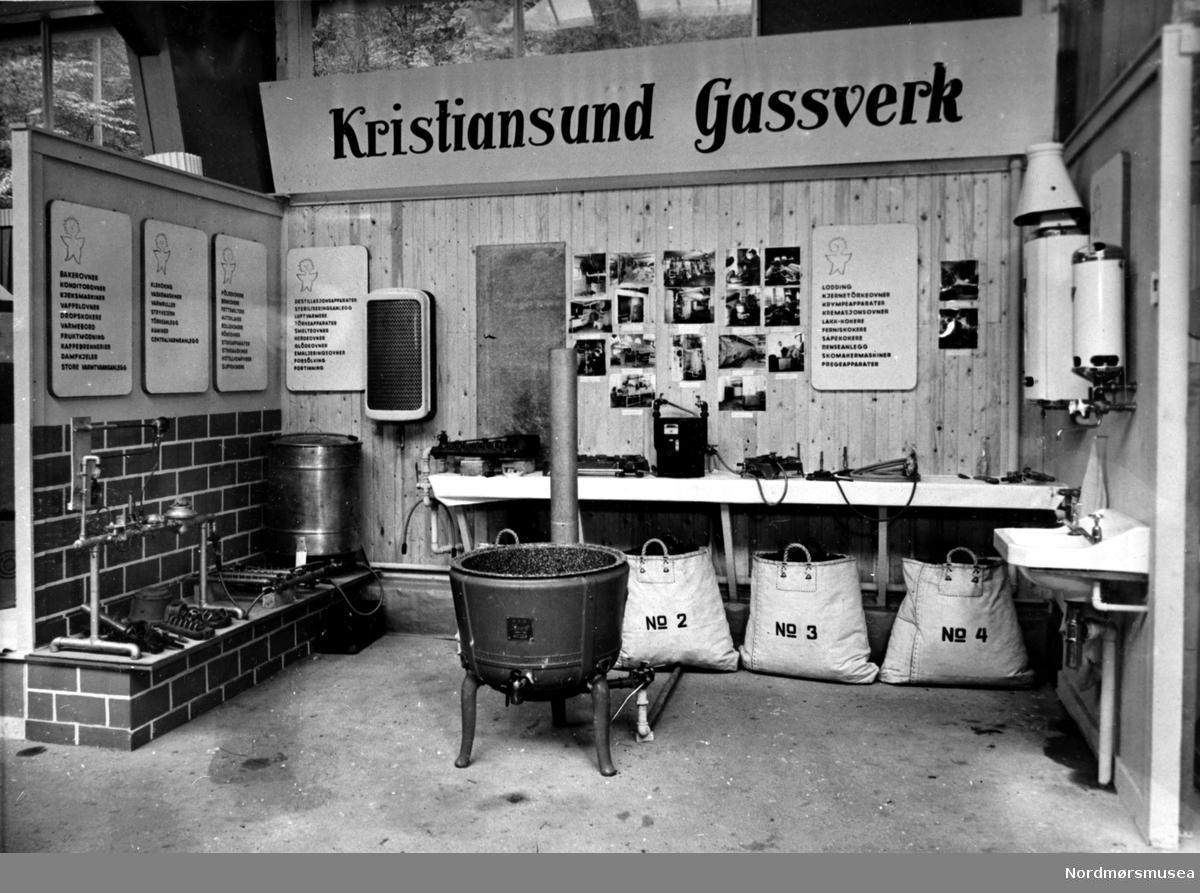 Inform. A L Tømmervåg: Den 7. sept. 1907 ble A/S Kristiansunds Gasverk konstituert, etter at bystyret den 17. juli samme år hadde meddelt Ferdinand G. Juell om konsesjon på anlegg og drift av et lysverk - elektrisitetsverk.  Dir. C. Phil var egentlig konsesjonssøkeren- og var den første driftsbestyrer, og han utarbeidet planene for anlegget og startet aksjeselskapet.  Anleggsarbeidet startet våren 1908 og driften ble igangsatt allerede 9. sept. 1908.  Anleggeskapasiteten var på 4000 kbm. pr døgn med mulighet for 6000 kbm.  Det elektriske anlegget ble påbegynt i 1908 og satt i drift i mars 1909.  Anlegget leverte lys og kraft til Kirklandets bebyggelse frem til våren 1921 da det ble avløst av kraftanlegget på Skar.  Gassen ble populær.  De gamle petroleumslampene i gatene ble erstattet med gasslykter, forsynt med Arubrennere på 60 normallys.  På det meste var det 324 lykter.  Til husholdningsbruk ble gassen mye brukt.  Det startet med 547 abonement og i 1932 var det økt til 2442 abonem.  Gassverket gikk godt, men de to siste årene under første verdenskrig ble vanskelig da det var kullmangel og prisene på kull var svært høye.  Selskapets første styre besto av Fredrik Selmer, formann, C. Kaurin, Nic. Volckmar styremedlemmer.  Gassverket fikk store ødeleggelser under bombingen av Kristiansund i 1940.   Fra Nordmøre Museum sin fotosamling. EFR2015