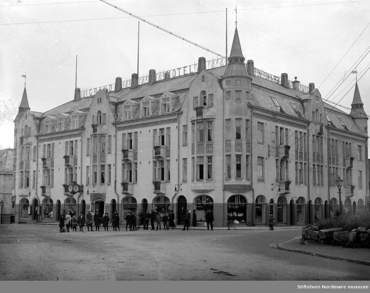 """Et meget flott bilde av byens andre Grand Hotell. Byens første Grand Hotell var bygd i sveitserstil, men 8. november 1907 brant denne ned til grunnen. Eieren av hotellet Nils Nilsen valgte senere arkitekt Kristen Tobias Rivertz fra Kristiania til å bygge opp hotellet. Rivertz oppholdt seg da i perioden 1907-1909 i Kristiansund, hvor han blant annet har tegnet """"en Badeanstalt"""", Festiviteten, Grand Hotell og Norges banks lokaler i samme gaten som Grand Hotell. Hotellet ble oppført av murmesterfirmaet Olsen & Michalsen i Jugendstil, og under Rivertz' ledelse og tegninger. Hotellet kostet litt over 200.000 kroner å bygge, men summen inkluderer ikke tomten og monteringen (Referanse: En oplevelsens festlabyrint av Egil Husby, side 15 - 17). Byens andre Grand Hotell brant under bybrannen 28. april 1940, da tyskerne brente store deler av Kirkelandet ned til grunnen. Fra Nordmøre Museums fotosamlinger"""