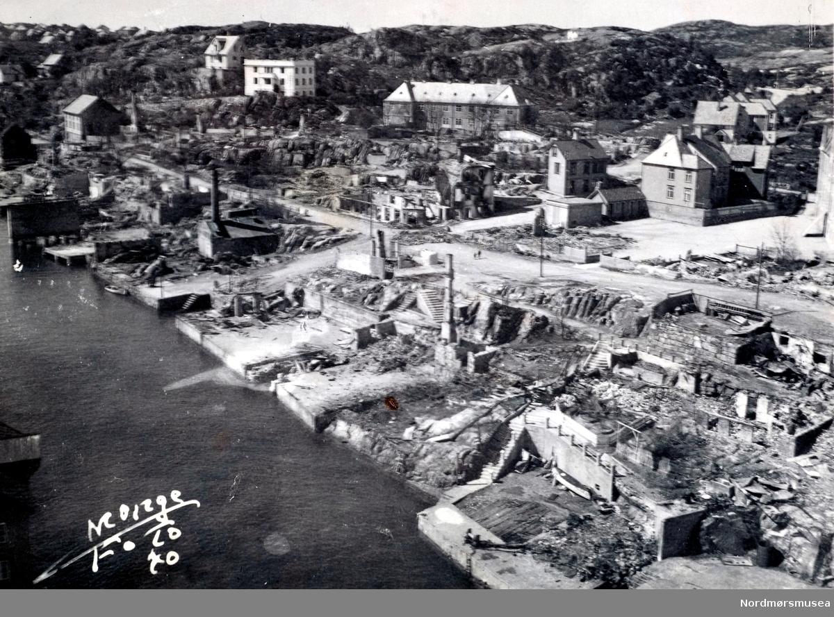 """Krigen har her kommet til Strandgata på Gomalandet i Kristiansund, hvor vi ser fra venstre i bakgrunnen bedehuset, Hunneshuset og det lange bygget kjent som Arken. Etter nazistenes herjinger i perioden 28. april til 1. mai 1940 ligger nå store deler av byen i ruiner. Det totale antall brente bygg var 767, hvor 605 av disse var på Kirkelandet og 162 på andre """"land"""" i Kristiansund. Her fantes det til blant annet til sammen 3906 boliger ifølge boligtellingen av 1938, og av disse brant 2162 boliger ned og 7099 mennesker ble husløse. I tillegg til de 767 brente byggene brant 36 fiskepakkehus ned til grunnen, hvorav 34 lå på andre """"land"""". Verdien av de brente byggene beløp seg til kroner 26,9 millioner for Kirkelandet (kroneverdi per 1940) eller tilsammen 30,6 millioner kroner (kroneverdi per 1940) for hele byen. Fra Nordmøre Museums fotosamlinger. Kilde: Gjenreisningsproblemer i Kristiansund. Fremlagt ved gjenreisningsinstituttet i Kristiansund. Juli 1945. Side 16 . Nordmøre museums fotosamling. dublett?"""