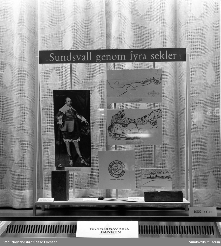 Skandinaviska bankens olika skyltningar. 1-2: Bilder och föremål från Liberia i Västafrika där Grängesbergsbolaget drev järnmalmsgruva i berget Nimba. 3: Guldgjutning. 4-5: Historiska bilder och föremål om Sundsvall under fyra sekler.