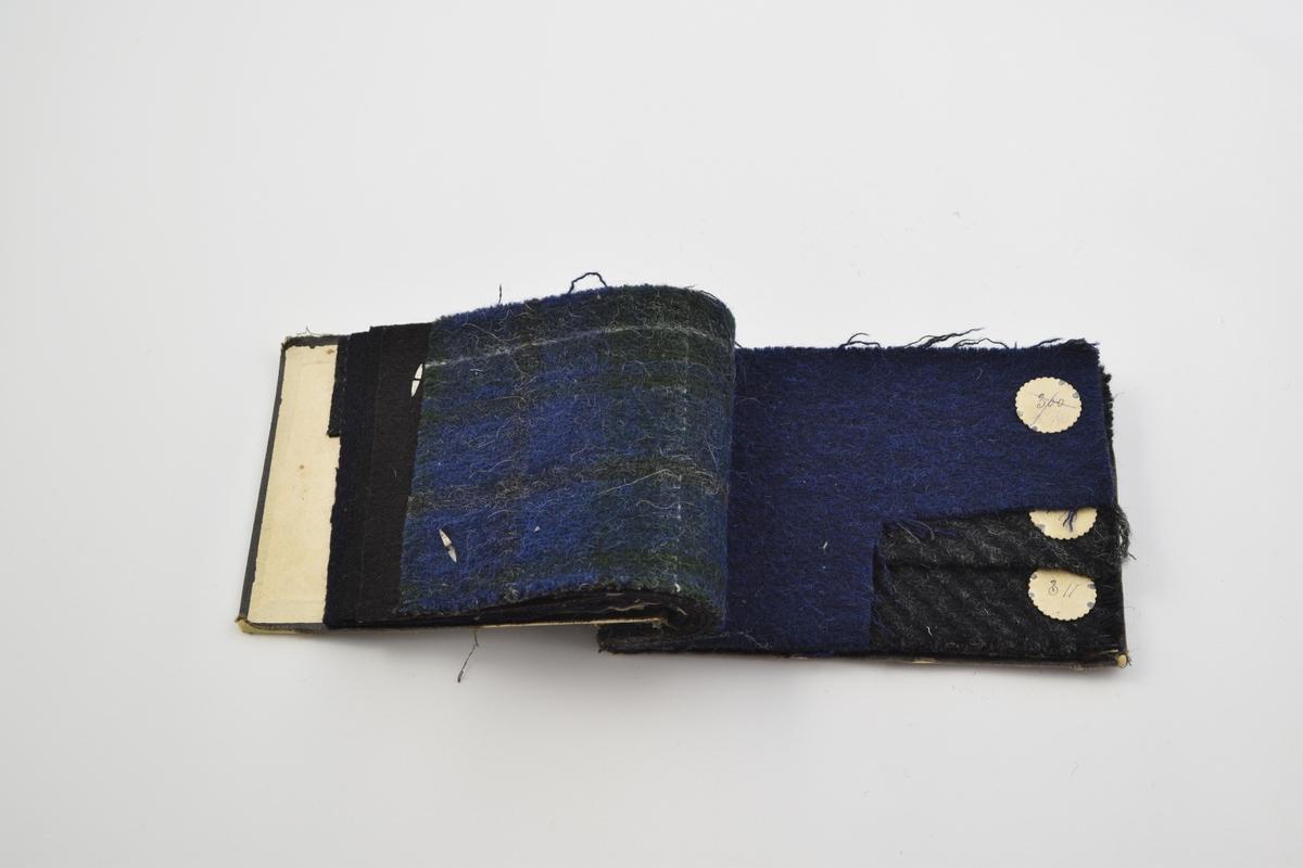 """Prøvebok med 11 prøver. Tykke stoff. Stoff nr. 301 (grått), 302 (mørke blått), 303, (brunt), 441 (grått), 245 (grått), 300 (eller 5/90 som skrevet med hånd, blått stoff), 198 (grått), og 311 (grått).  Noen av stoffene har rutemønster på baksiden. Det er notert """"utgått"""" på stoff nr. 303."""