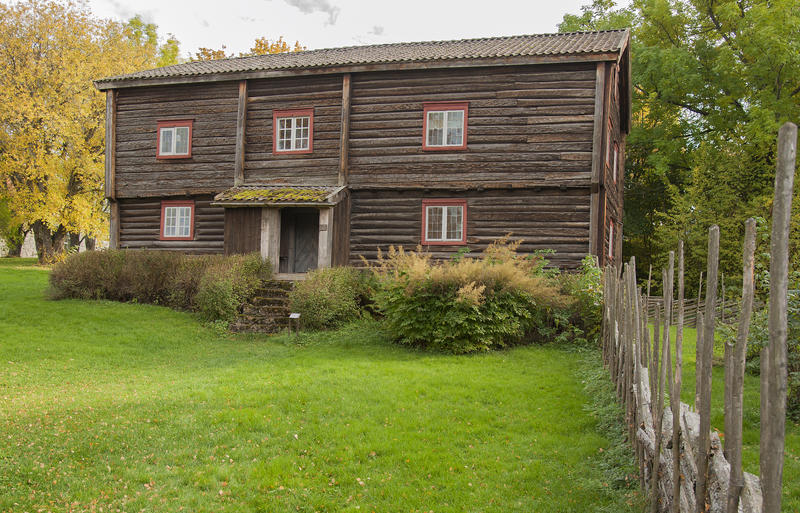Skøienbygningen er en tømmerbygning i to etasjer med inngang på midten. Grått tømmer, røde planker rundt vinduene. En skigard fører fram mot huset. (Foto/Photo)