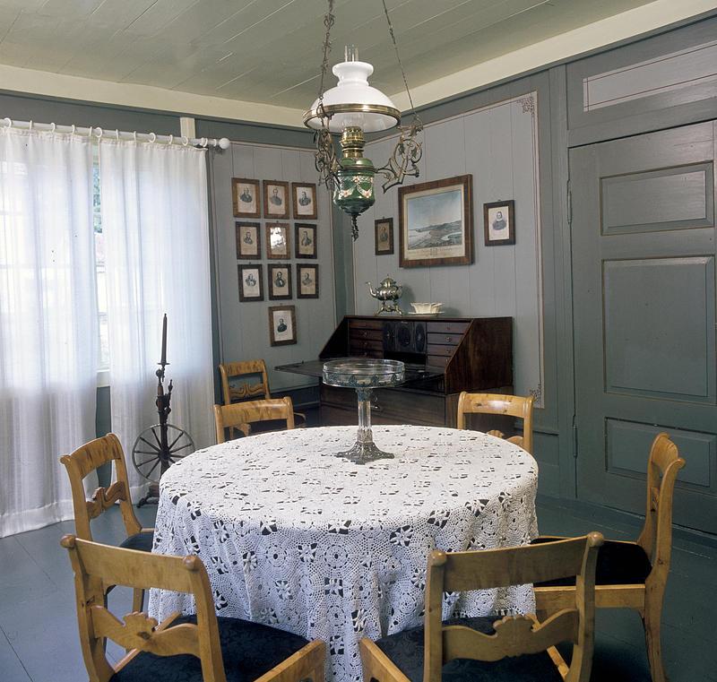 Interiør; rundt bord med hvit duk og stoler rundt i forgrunnen, husordel, mange fotografier på veggen og en oljelampe over bordet.