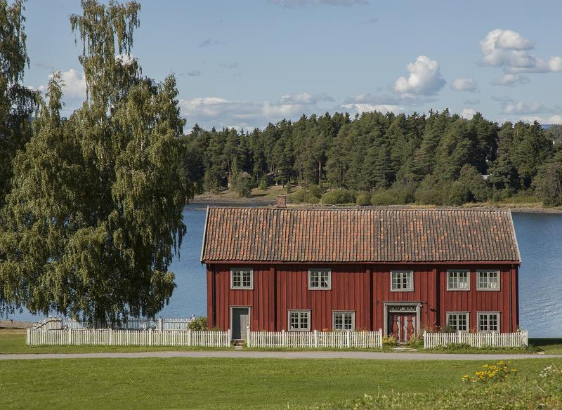 Stor, rød bygninge i to etasjer ligger bak et hvitt stakittgjerde ned mot vannet. På venstre side to bjørker. (Foto/Photo)