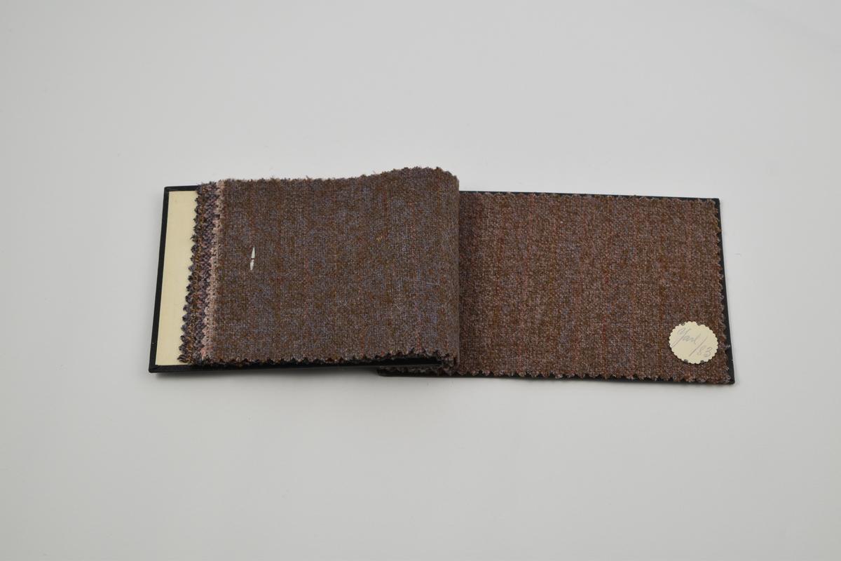 """Prøvebok med 6 prøver. Middels tykke ullstoff med diskret mønster, særlig i form av striper. Denne prøveboken inneholder flere ulike designnummere av kvaliteten """"Jarl"""". Alle stoffer er merket med en rund papirlapp festet med metallstifter hvor nummer er påskrevet for hånd.  Stoff nr.  Jarl/41 (fiolett), Jarl/54 (brun), Jarl/57 (fiolett), Jarl/67 (rosa), Jarl/82 (brun), Jarl/83 (brun)."""