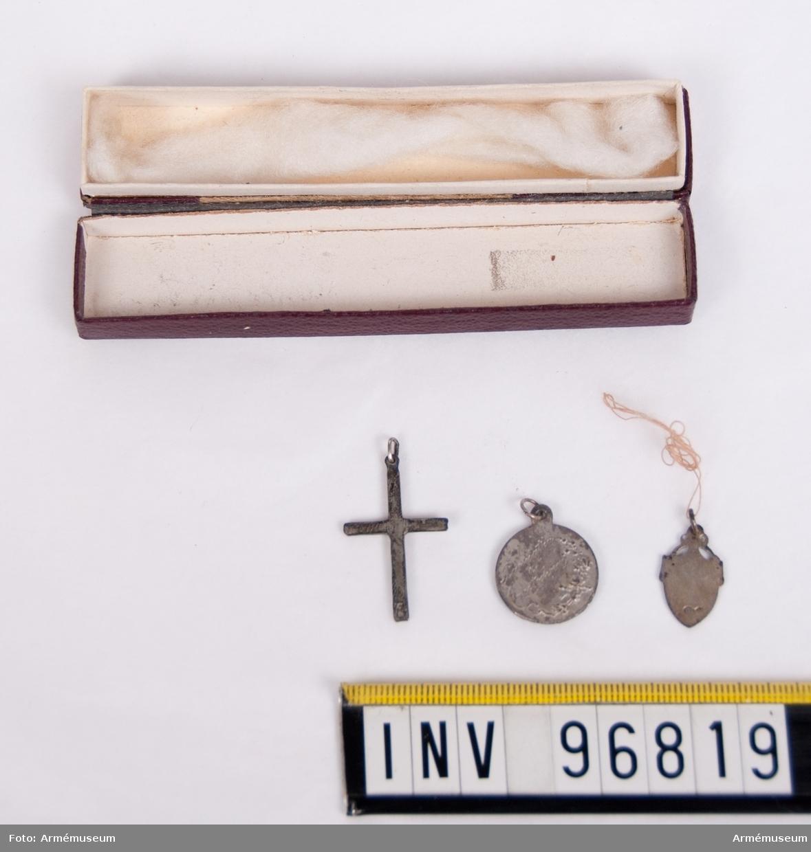 Tre halssmycken i liten avlång brun pappask med läderimitation. Ett krusifix och två helgonbilder.