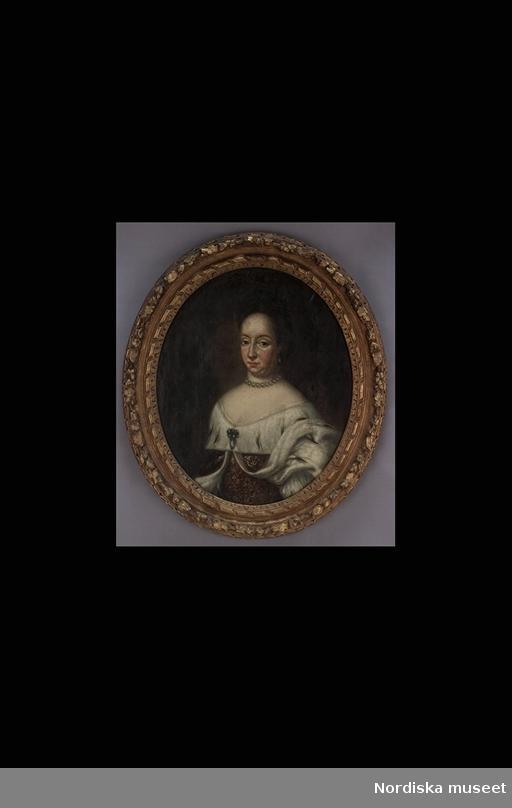 """Huvudliggaren: """"Ulrika Eleonora, porträttmålning, oval. Enligt anteckning på baksidan (CL) av Ehrenstrahl. Köpt i Stockholm 1893. Renoverad, lagad. Oval, skuren, krederad och förgylld ram av furu. h 94, br 81 cm."""""""