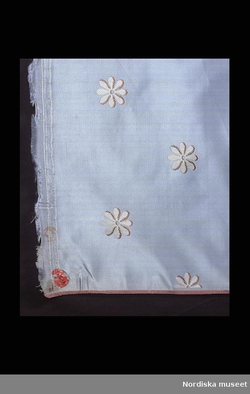 """Huvudliggaren; """"Tygrulle, siden. Blå parpsatin, lanserat mönster kypert. Blå botten, vita sexflikiga blommor, bruna konturer. Stockholms hallstämpel svart, röd lackstämpel. Tillverkad ca 1810."""""""