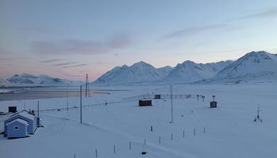 Blått fredet hus med fjell på Svalbard