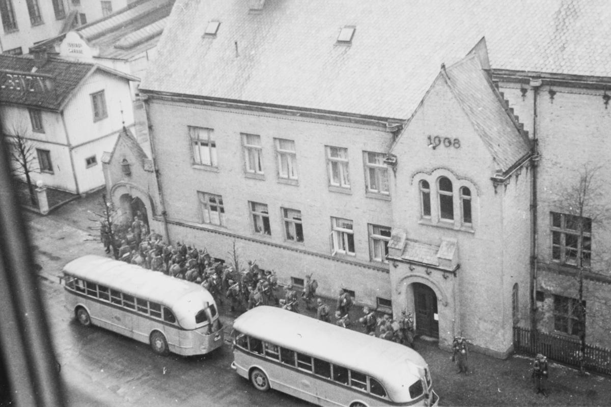 Tyske tropper rykker inn på Majorstuen skole som skal brukes som kaserne. Bussene i forgrunnen var rekvirert  fra Oslo Sporveier til troppetransport.
