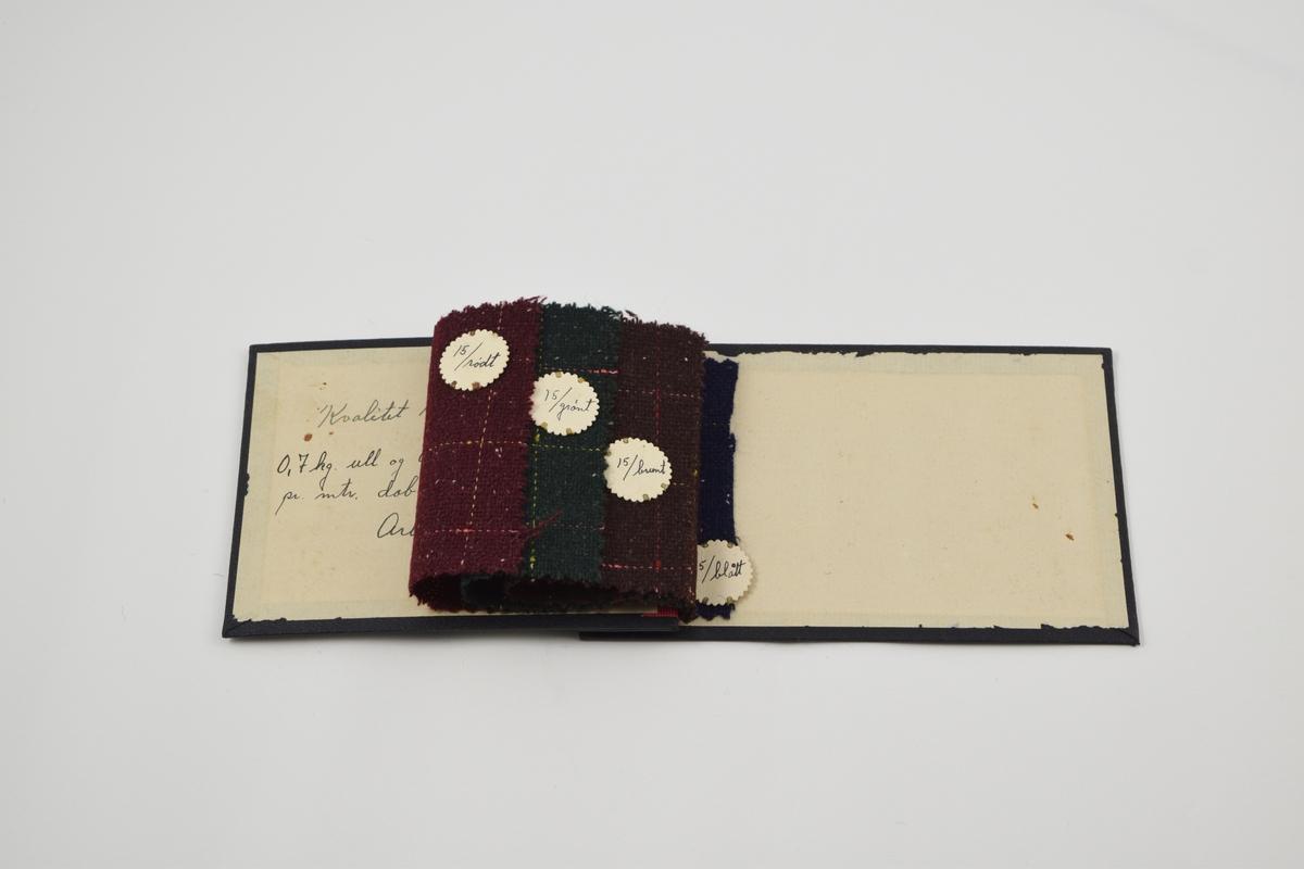 Prøvebok med 4 prøver. Middels tykke ullstoff med ruter av rød og gul tråd.  Den siste prøven er klippet i så bare en liten del er igjen i boken og merkelappen er festet til det gjenværende stoffet. Alle stoffer er merket med en rund papirlapp festet med metallstifter hvor nummer er påskrevet for hånd.  Stoff nr. 15/rødt, 15/grónt, 15/brunt og 15/blått.