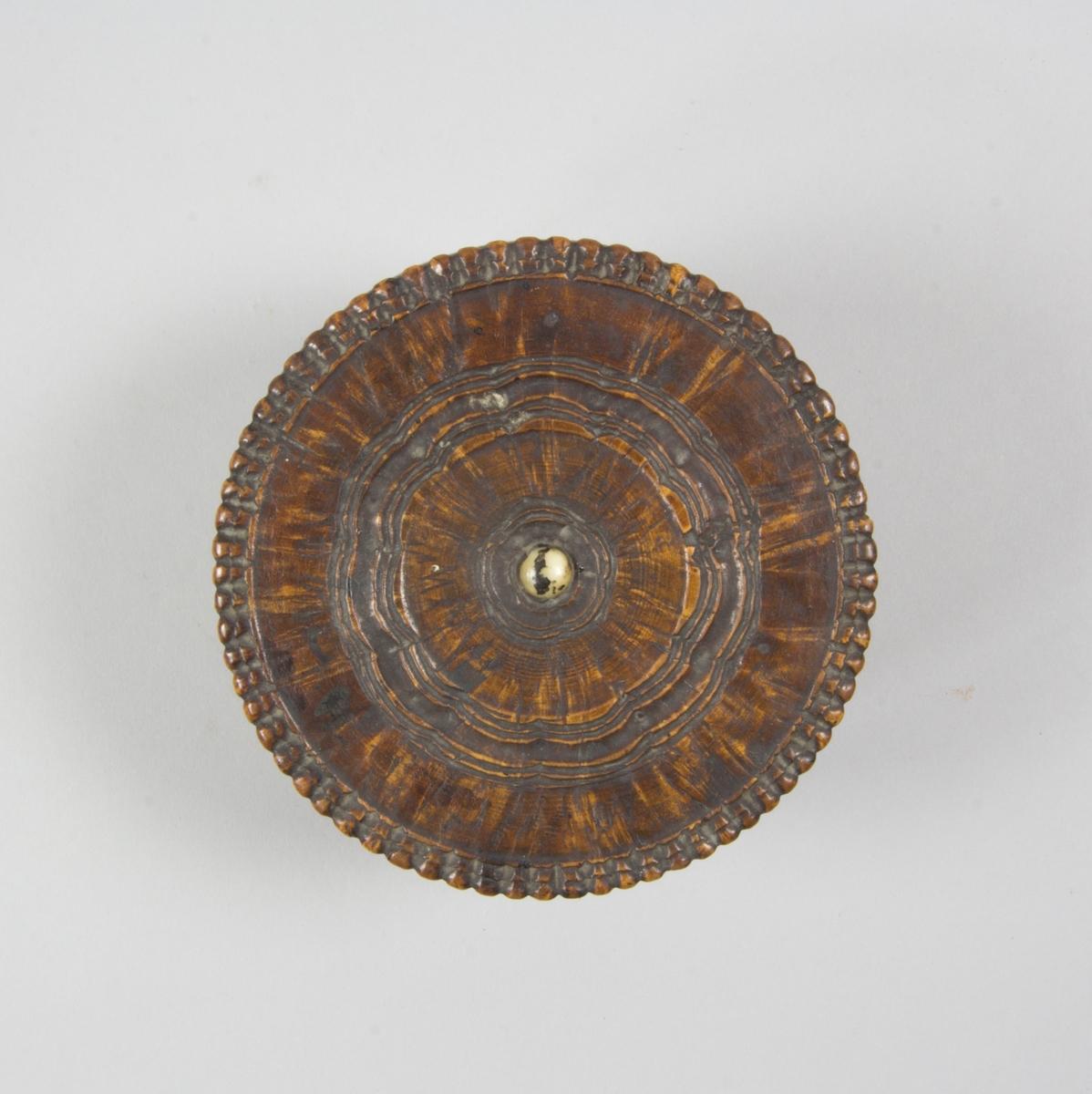 Svarvad rund ask av trä med löst utanpåliggande lock. På locket en lockknopp av ben. Skuren dekor runt lockknoppen och pärlstavsliknande dekor runt kanterna. I asken rester av röd plastelina samt bläck.