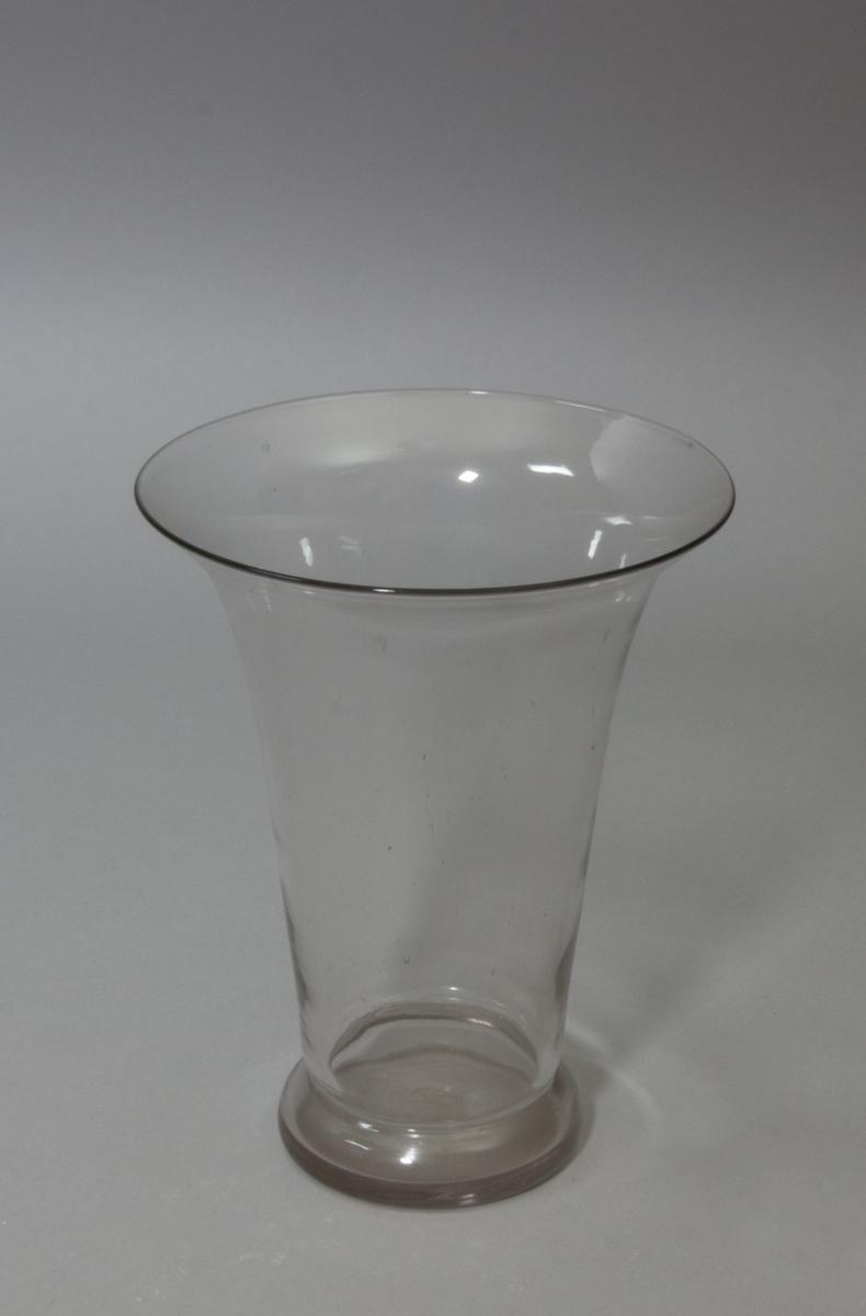 Blomglas i bägarform med utvikt mynning. Klart glas.