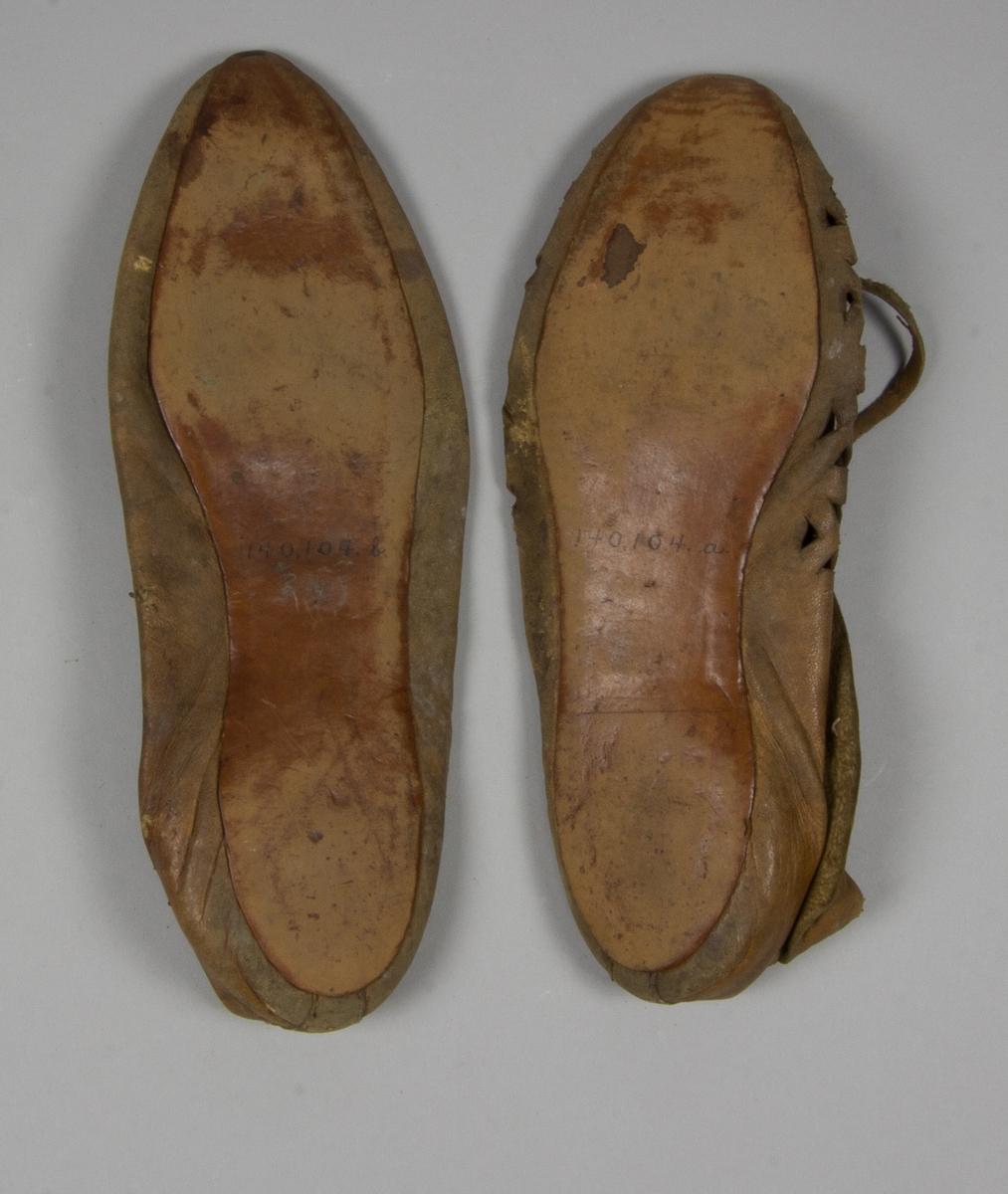 Skor, 2 st av brunt skinn, av mockasintyp. Den ena med genombruten ovansida och nedvikt skaft samt band under det nedvikta skaftet. Tunn sula. Den andra skon med tunn sula och snörning med grovt snöre.