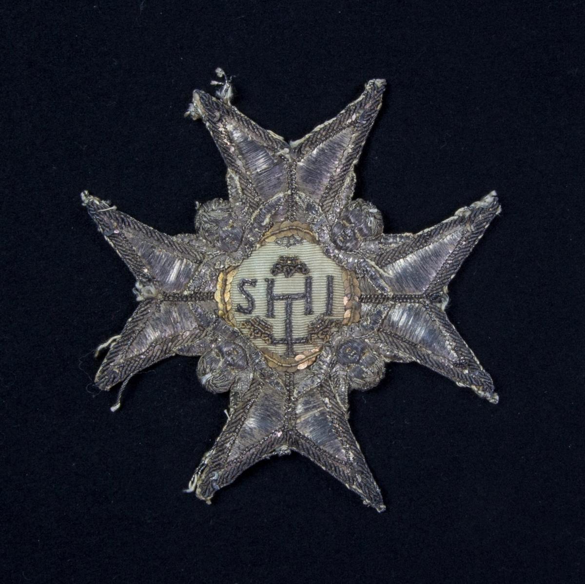 Serafimerordensstjärna med 8 uddar av ljust skinn med broderade ornament av silvertråd, såsom änglahuvuden med mera. I centrum IHS broderat på siden omgivet av paljetter.