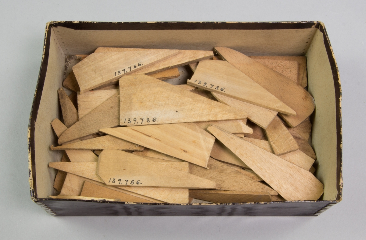 Ask av svart papp, förstärkt i hörnen med metall. Innehåller ett 30-tal kilar av trä till spännramar.