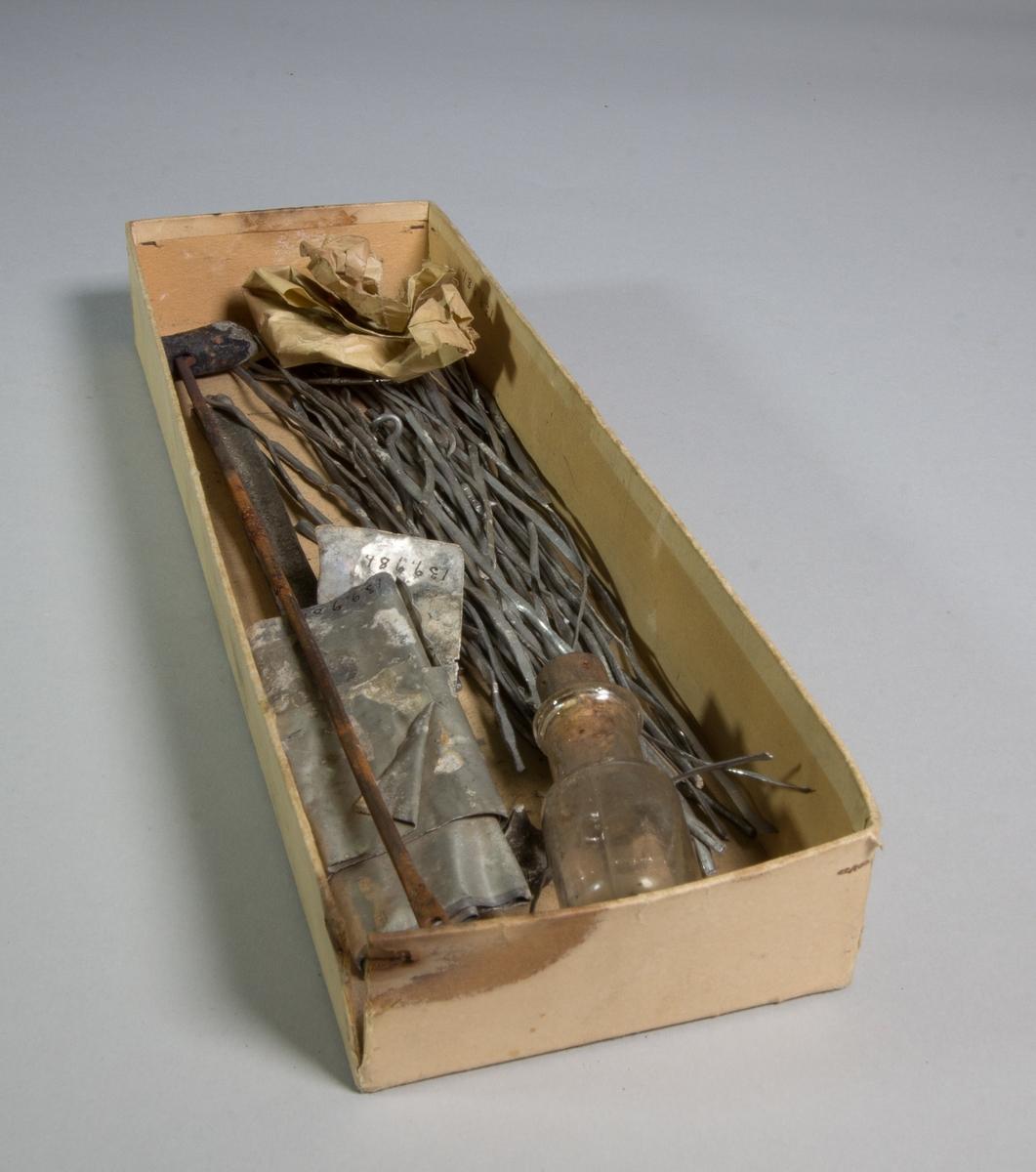 Lödkolv av metall bestående av lång ten och ytterst rektangulär och avfasad del. Lödkolven ligger i en papplåda som även innehåller ett antal bitar av lödtenn samt en glasflaska med kork.