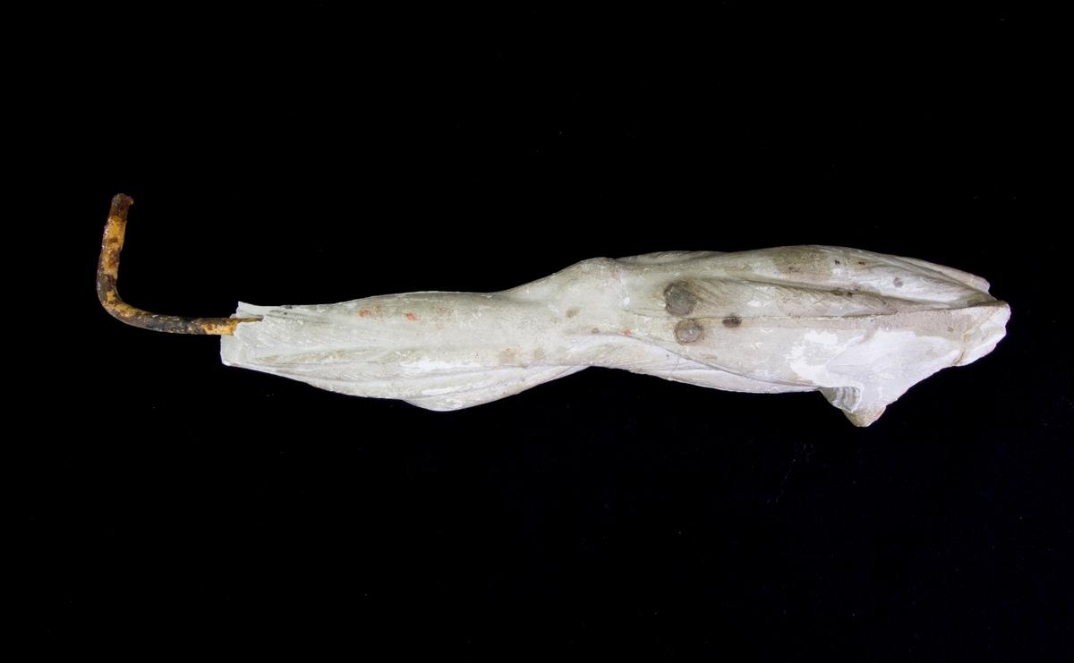 Studiemodell av gips föreställande ett mansben med väl utformade muskler. Benet uppbyggt kring en ten av järn, rostig.