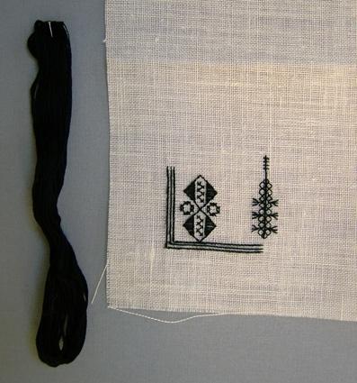 """Påbörjat broderi till broderad löpare komponerad av Anna Hådell.Broderiet finns med i boken """"Svartstick"""" från 1980.Här anges material: Vitt linne, 14 trådar/cm och moulinegarn nr 25/6 svart. Teknik: Rutsöm, rätlinjig plattsöm, korsstygn, tofssöm och dubbla förstygn. Har sålts som materialsats + skiss mm-papper. WLHF-1386:1 - Något gulare linne. Tillbehör 1 svart garn-docka moulinegarn, utan etikett."""