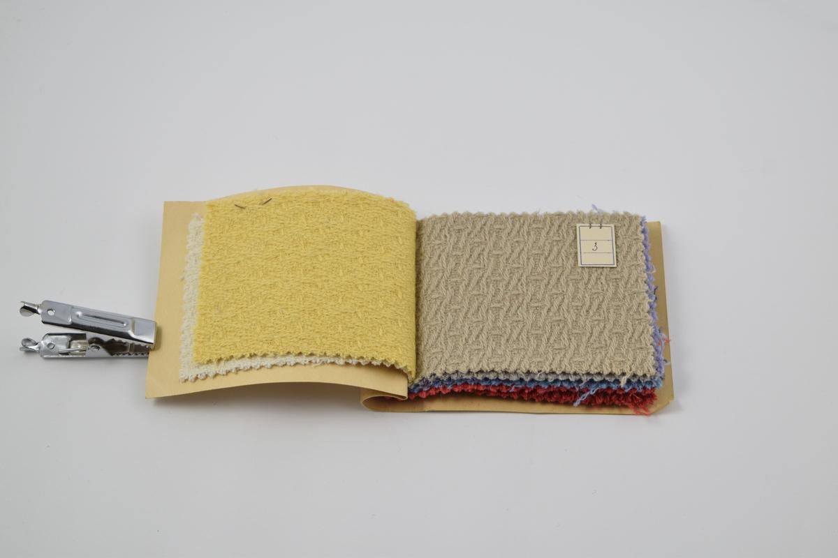 Prøvebok med 11 prøver. Middels tykke ensfargede ullstoff med utpreget vevmønster. Alle stoff er merket med en firkantet papirlapp festet med metallstifter hvor designnummer er påskrevet for hånd. Kvalitetsnummeret for hele boken er skrevet på innsiden av papiromslaget.     Stoff nr. 6150/1 (hvit), 6150/2 (gul)), 6150/3 (beige), 6150/4 (grå), 6150/5 (fiolett), 6150/6 (blå), 6150/7 (rød), 6150/8 (rød), 6150/9 (blå), 6150/10 (brun), 6150/11 (grønn).