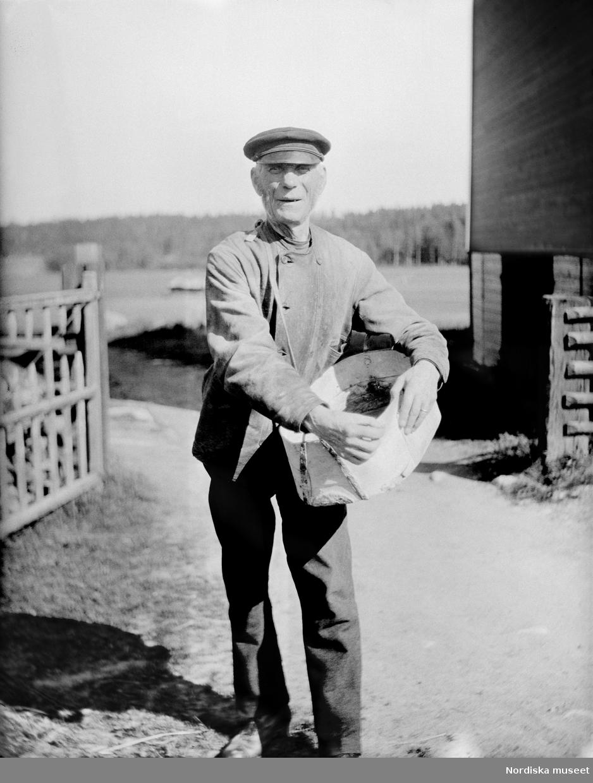 Såning ur skäppa i Hedsta by, Hälsningland. Äldre man står på en gårdsplan med en skäppa under armen.
