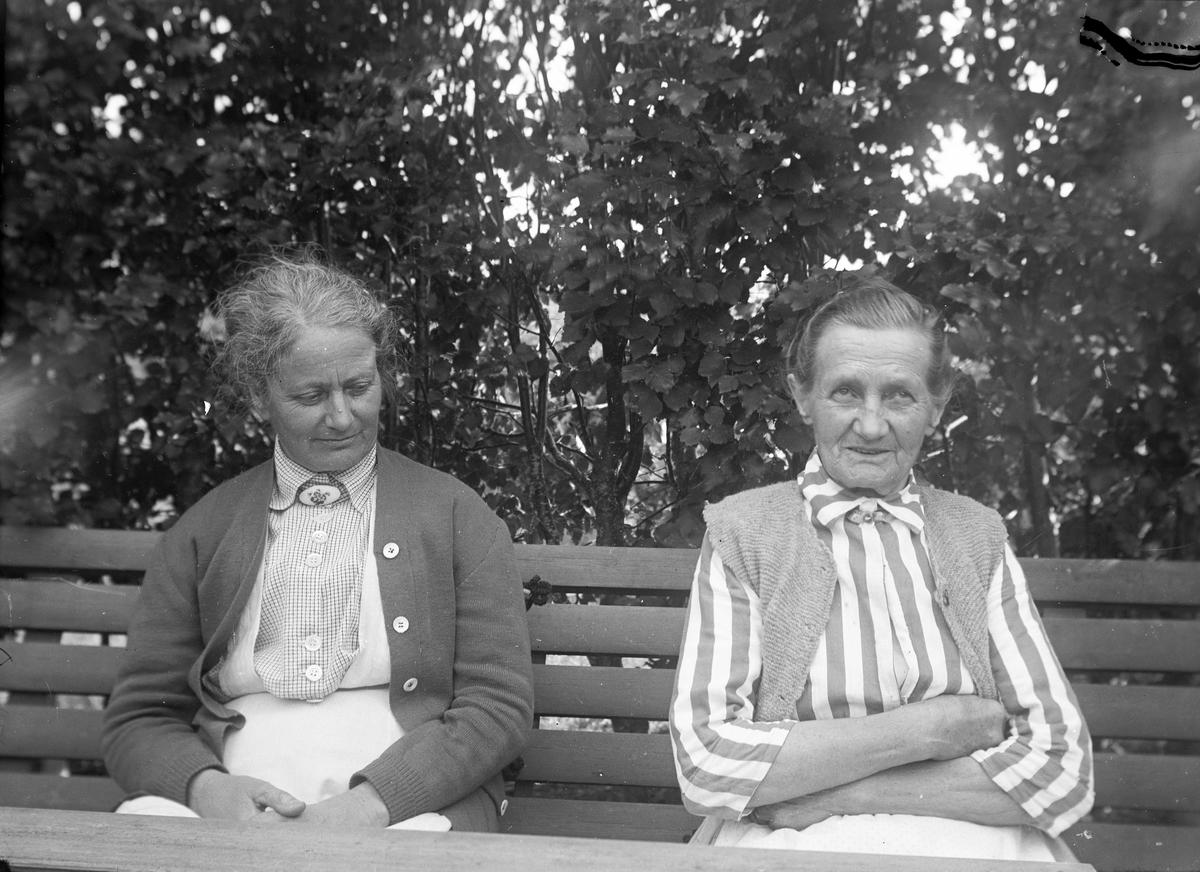 Två damer i trädgården. Tidsomfånget är 1900 - 1940