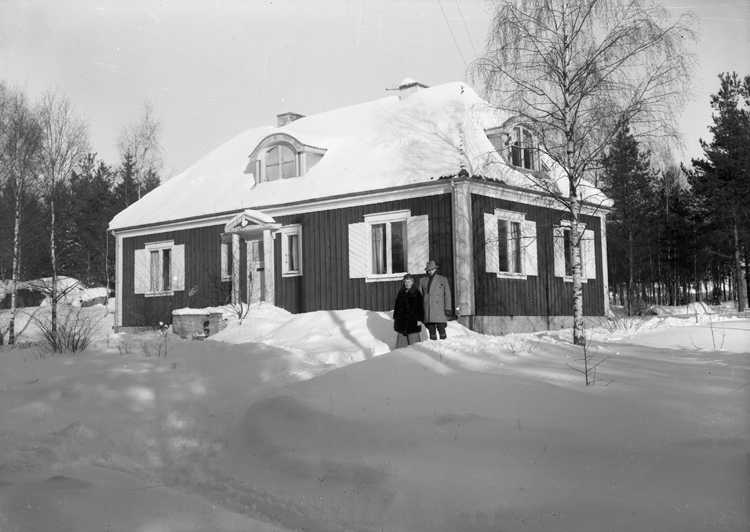 Foto av ett bostadshus. Vid ena knuten står en man och en kvinna. Vinterbild.